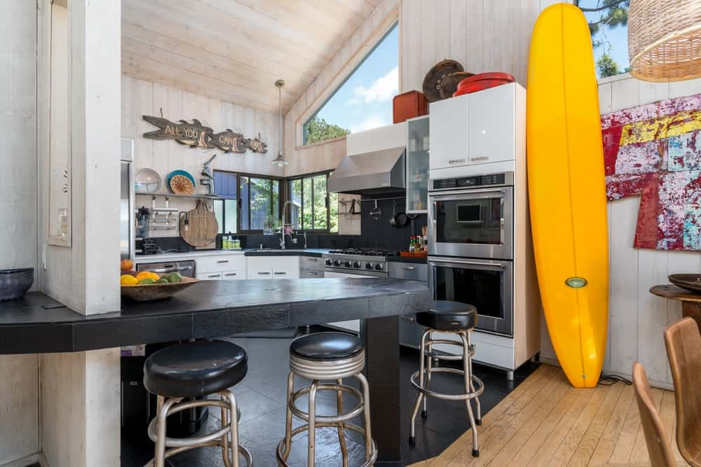 This other kitchen has a homey quality to its black breakfast bar that is paired with modern stools matching the black flooring of the small kitchen.