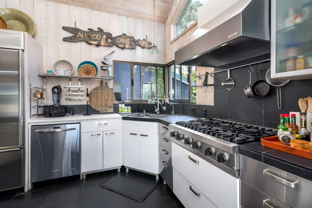 This black theme extends to the countertop and backsplash of the cabinetry lining the walls topped with a bright transom window.