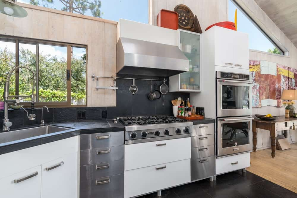 The cabinetry lining the walls house the various stainless steel appliances that stand out against the white drawers.