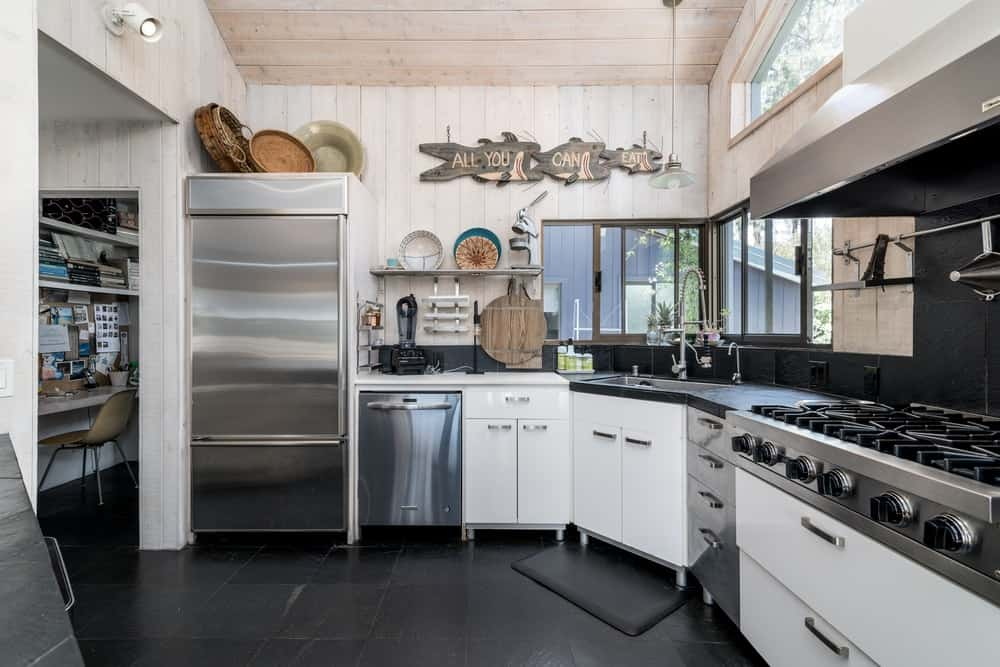 There is also a large stainless steel fridge by the edge of the cabinetry that is topped with rustic decorations.