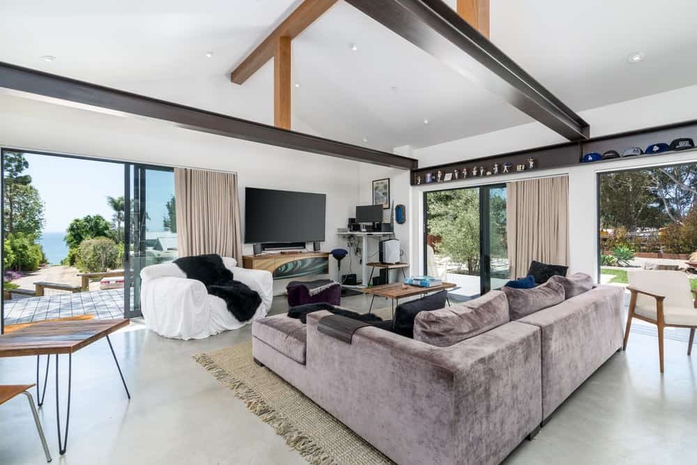 The living room has a tall white cove ceiling with exposed wooden beams for contrast and support.