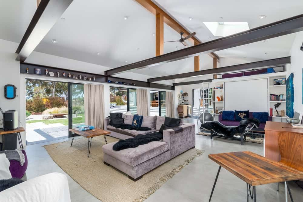 The large room houses two living room areas under the large cove ceiling.