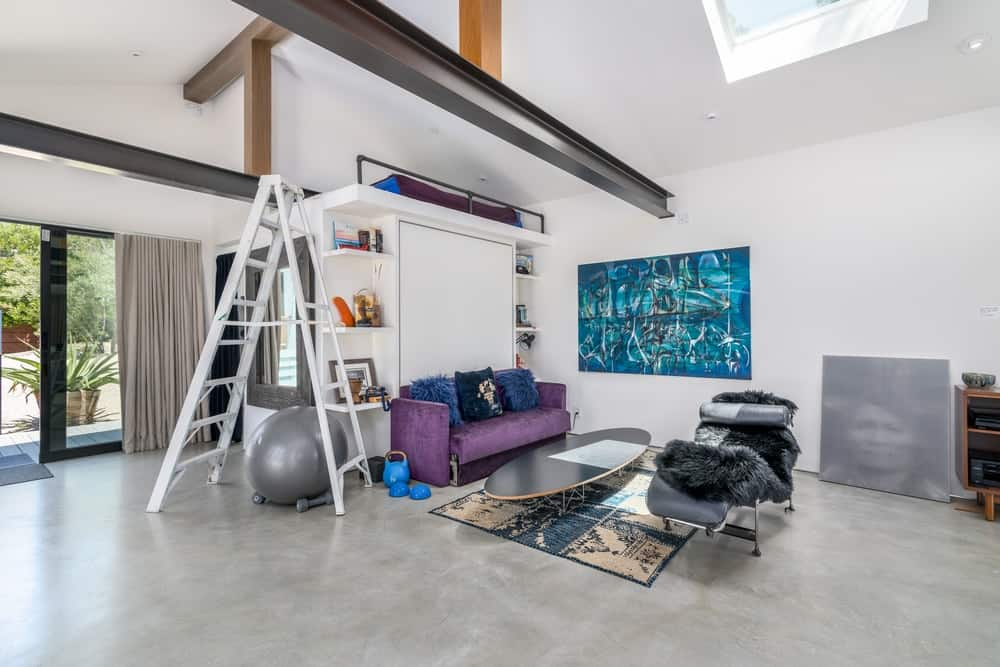 The other has a more intimate vibe with a purple couch and a surfboard coffee table.
