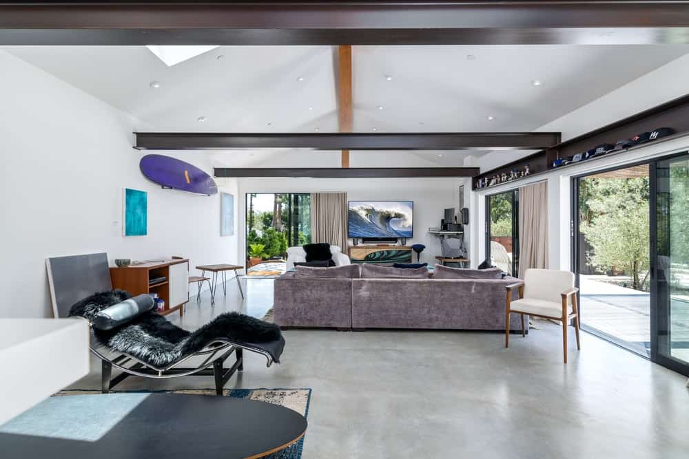 One has a large L-shaped sectional sofa that stands out against the industrial-style concrete flooring.