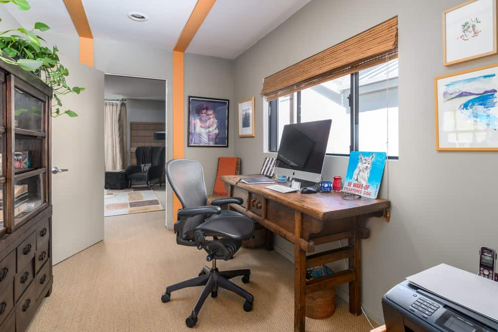 This house also has an office with a light hardwood flooring to match the dark wooden desk and the shades of the window.