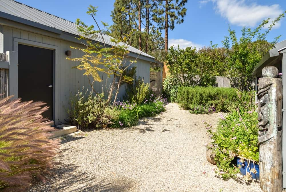 Upon entry of the outer gate, you are welcomed by beautiful landscaping surrounding a pebbled walkway.