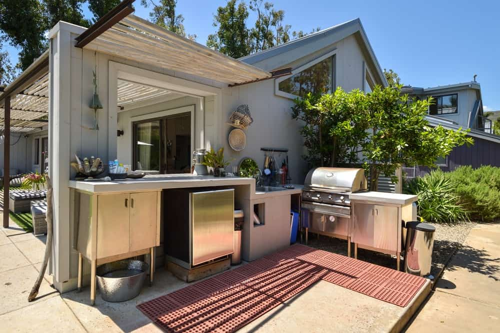 This is the outdoor kitchen filled with stainless steel structures and appliances.