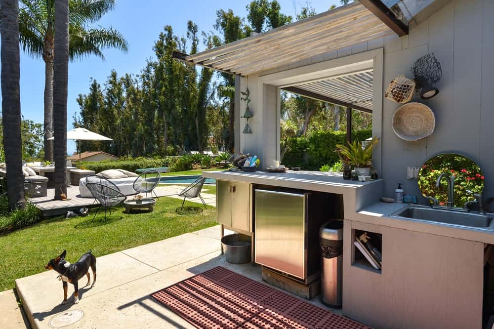 This outdoor kitchen has a clear view of the poolside area just a few steps away.
