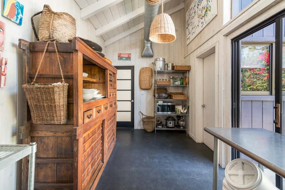 This charming and rustic area of the house has a large wooden structure with shelves and cabinets for storage of dishware.