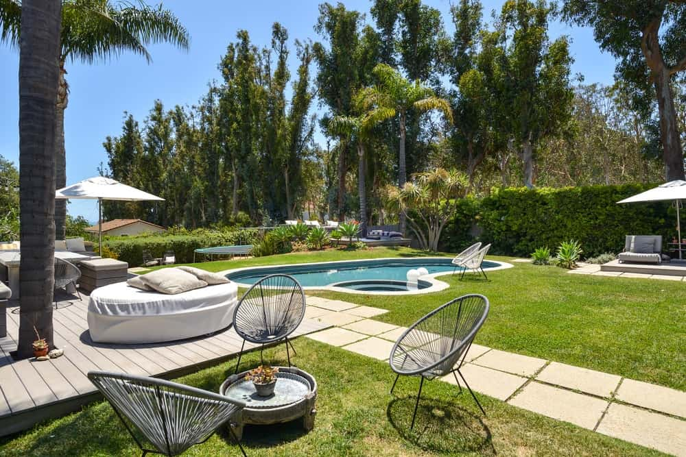 The beautiful pool side area has concrete stone walkways paired with green lawns of grass.