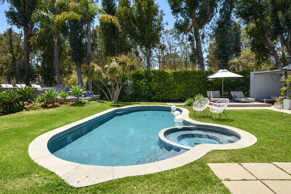 The pool is bordered on one side by tall hedges of shrubs and trees that serve as a beautiful background.