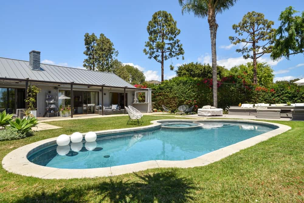 The other side of the pool also has a set of tall trees and tall hedges providing privacy for the area.