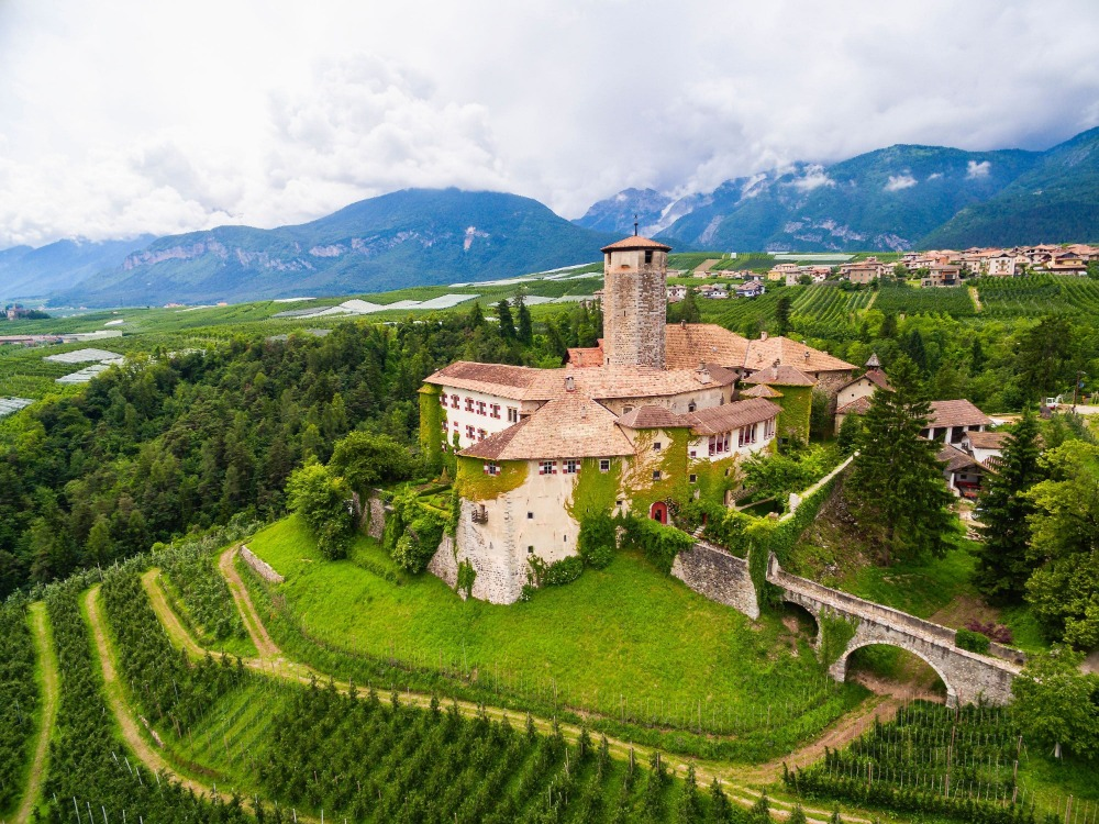 Aerial view of the Castel Valer in Tasullo, Italy boasting its medieval exterior and the lush landscape surrounding it.