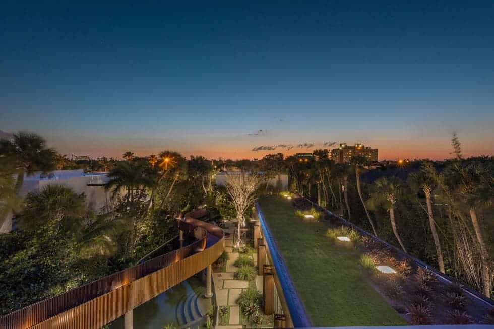 This is an aerial view of the elaborate slide that cruises over the tall trees of the backyard that has a large lawn of green grass adorned with outdoor lighting giving it a warm and welcoming tone. Images courtesy of Toptenrealestatedeals.com.