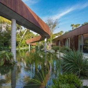 This Miami Beach Contemporary-style house has wooden slats to its exterior walls for insulation and perfectly matched with the long slide of the pool just outside its large glass walls that can open to combine indoor and outdoor areas. Images courtesy of Toptenrealestatedeals.com.
