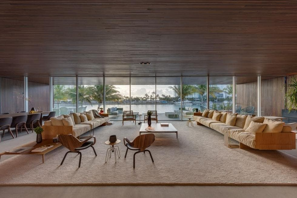 The house has a large great room with a wide wooden ceiling over the living room area that has two large sectional sofas with a great view of the outdoors through glass walls that can open and combine indoor and outdoor seamlessly. Images courtesy of Toptenrealestatedeals.com.