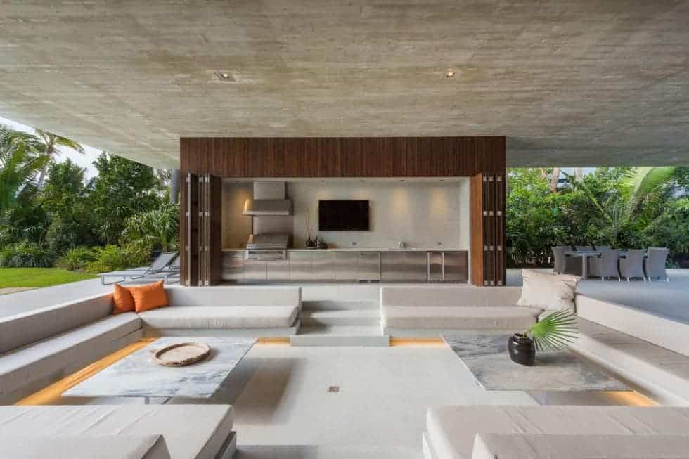 The Contemporary-style house has a covered area with open walls that give a lush scenic view of the outdoors. These can be enjoyed in the comfort of this sunken built-in seats with cushions and pillows paired with white marble coffee tables. Images courtesy of Toptenrealestatedeals.com.