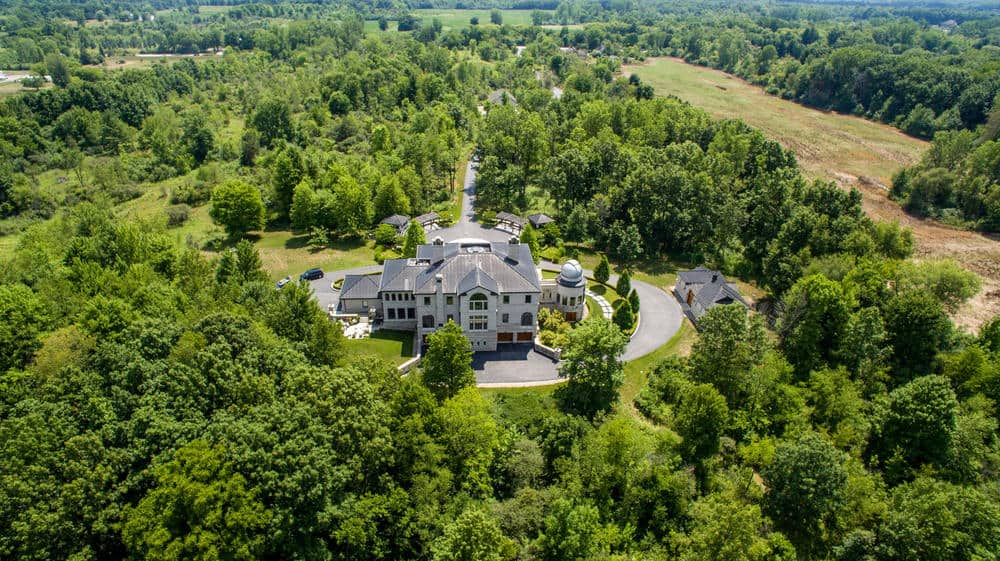 This aerial view of the mansion shows the small structure beside it across the driveway which is the workshop. You can also see here how the mansion stands out against its surroundings proudly. Images courtesy of Toptenrealestatedeals.com.