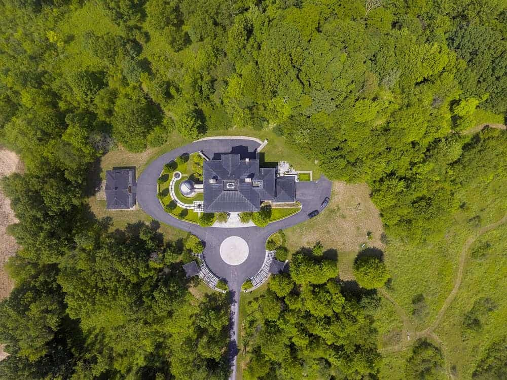 This aerial view of the mansion features its isolation and and surrounding lush landscape filled with tall trees. Images courtesy of Toptenrealestatedeals.com.