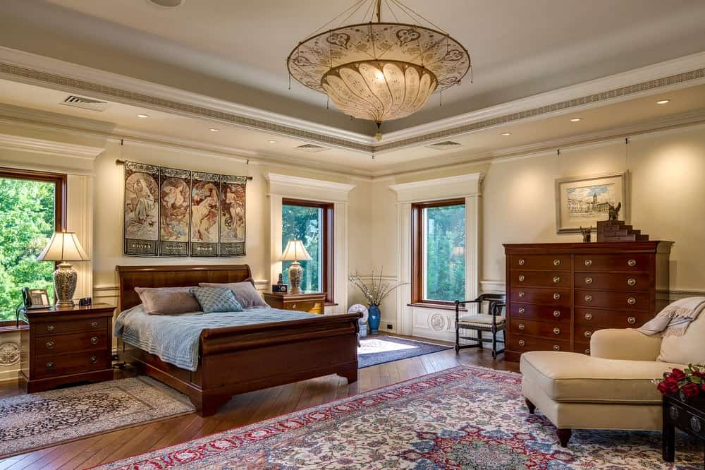 This is the primary bedroom that has a large wooden sleigh bed to complement the beige walls and tray ceiling that hangs a large dome lighting over the foot of the bed with a colorful patterned area rug. Images courtesy of Toptenrealestatedeals.com.