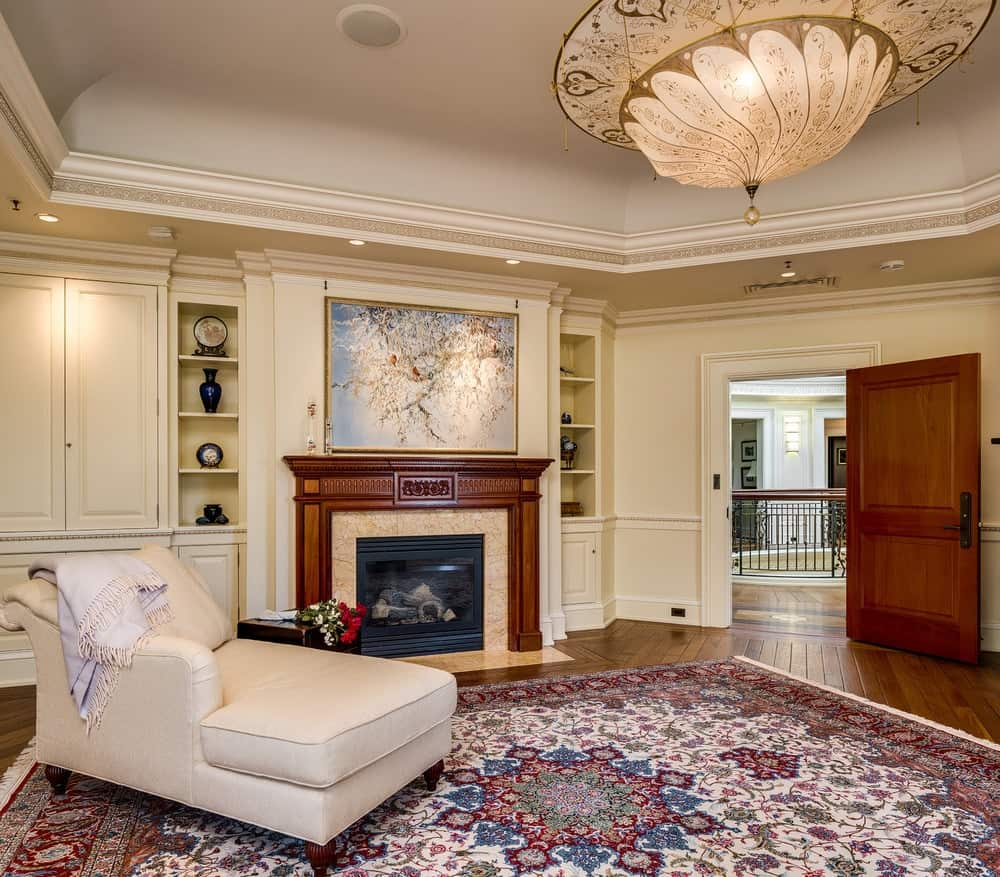 This is the foot of the bed where a comfortable reading nook is placed right next to the warm fireplace that has a wooden mantle topped with a wall-mounted artwork and flanked by built-in shelves. Images courtesy of Toptenrealestatedeals.com.