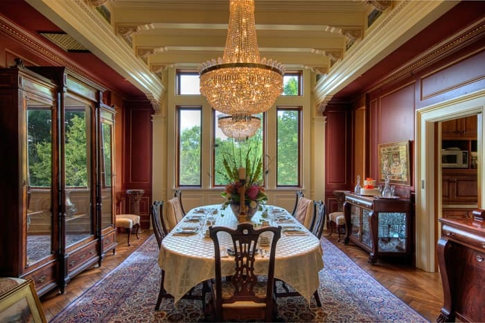 This is the formal dining room of the house with a large table covered in table cloth topped with a majestic chandelier that hangs from a beige cove ceiling with exposed beams illuminated by the large window on the far end. Images courtesy of Toptenrealestatedeals.com.