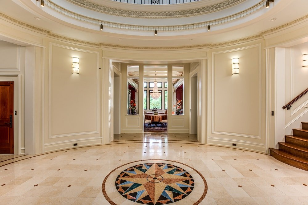 Upon entry of the house, you are welcomed by this elegant and simple foyer with beige walls and beige marble flooring adorned with a compass in the middle. Images courtesy of Toptenrealestatedeals.com.