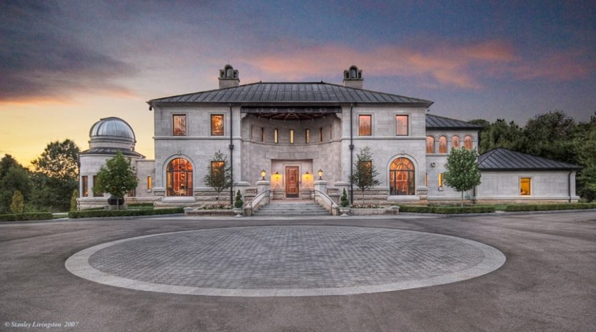 This is a closer look at the front of the house with a large concrete courtyard as a foreground. This then leads to a grand and tall main entry with wall-mounted lamps flanking the main door. Images courtesy of Toptenrealestatedeals.com.