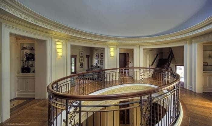 This is the indoor balcony with an elliptical shape, intricate wrought iron railings and surrounded by beige walls with wall lamps. Images courtesy of Toptenrealestatedeals.com.