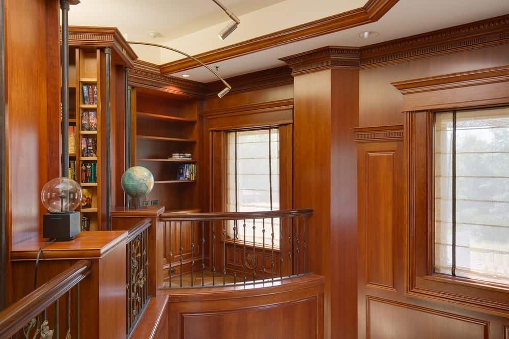 This is a look at the indoor balcony of the two-story library with wrought-iron railing supported by lush wooden posts. Images courtesy of Toptenrealestatedeals.com.
