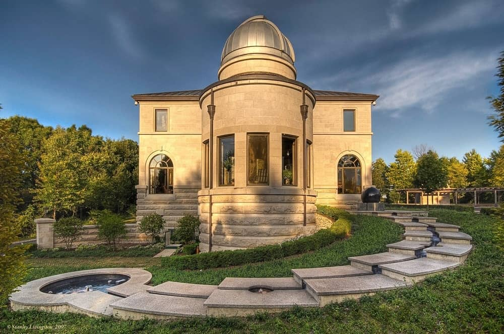 This is the front view of the observatory surrounded by lush green lawns of grass and tall trees traversed with a stone walkway leading up to the entry of the observatory. Images courtesy of Toptenrealestatedeals.com.