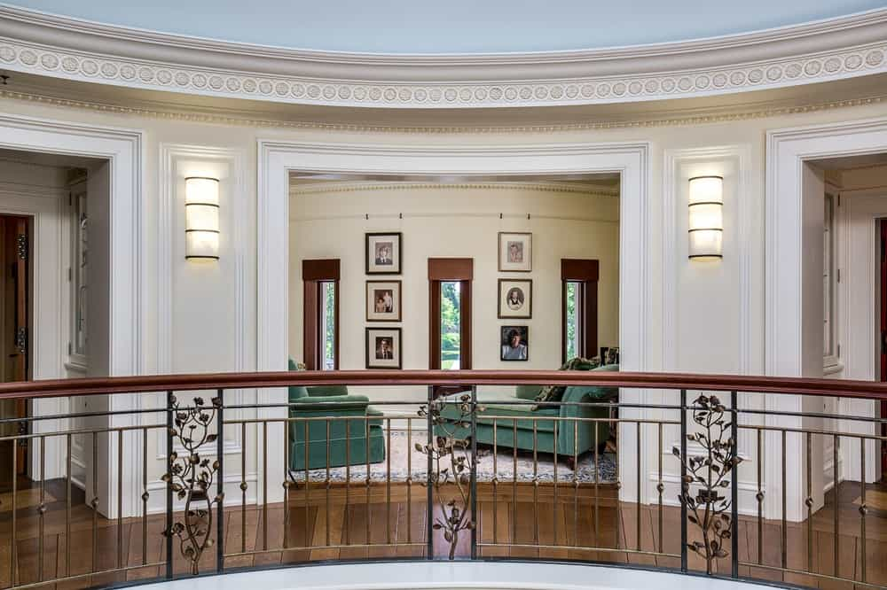 This is the indoor balcony that has intricate wrought iron railings and wooden banisters that match the flooring leading to the reading nook on the far side with a couple of green cushioned furniture paired with thin windows. Images courtesy of Toptenrealestatedeals.com.