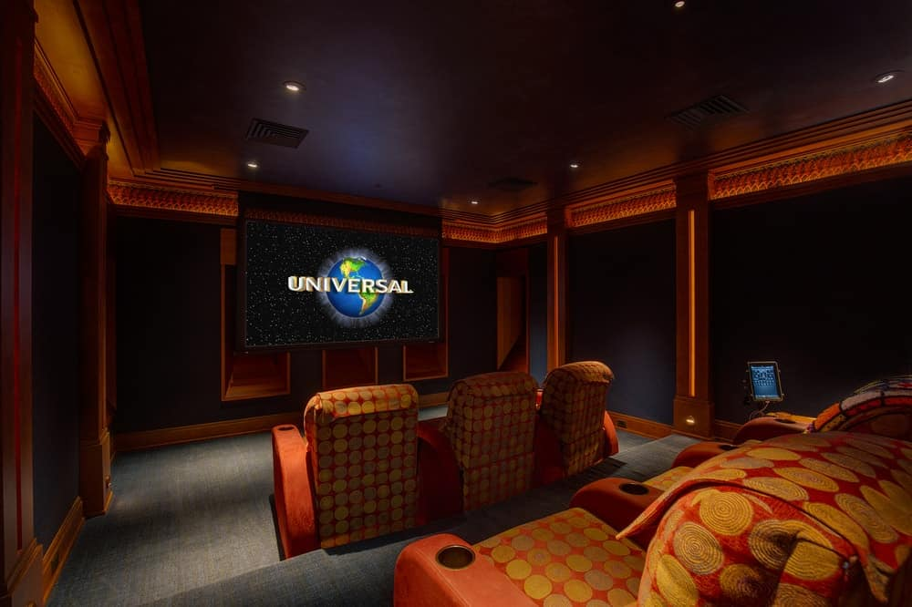 This is the home theater with comfortable cushioned chairs on platforms for an unobstructed view of the large screen that is complemented by the dark tones of the walls and ceiling. Images courtesy of Toptenrealestatedeals.com.