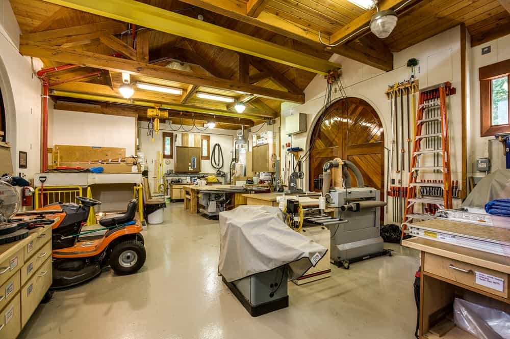 The large workshop has a spacious open floor space enough for high-powered machines. These are all topped with a tall wooden ceiling that has exposed wooden beams. Images courtesy of Toptenrealestatedeals.com.