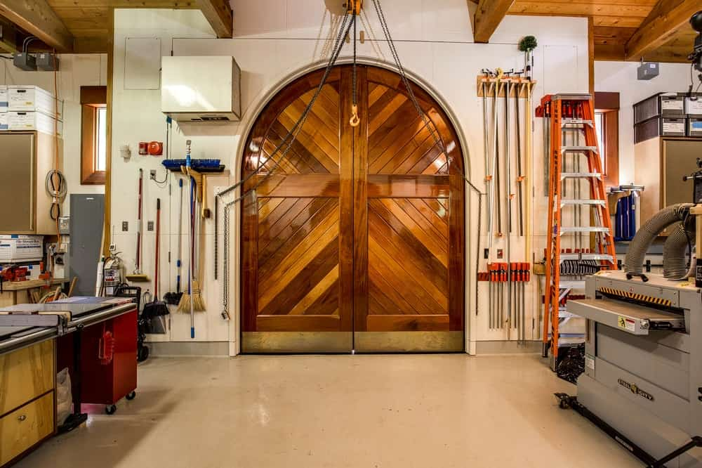 This is the gorgeous large arched wooden door of the workshop that pairs well with the wooden exposed beams of the ceiling. and complements the beige walls and flooring. Images courtesy of Toptenrealestatedeals.com.