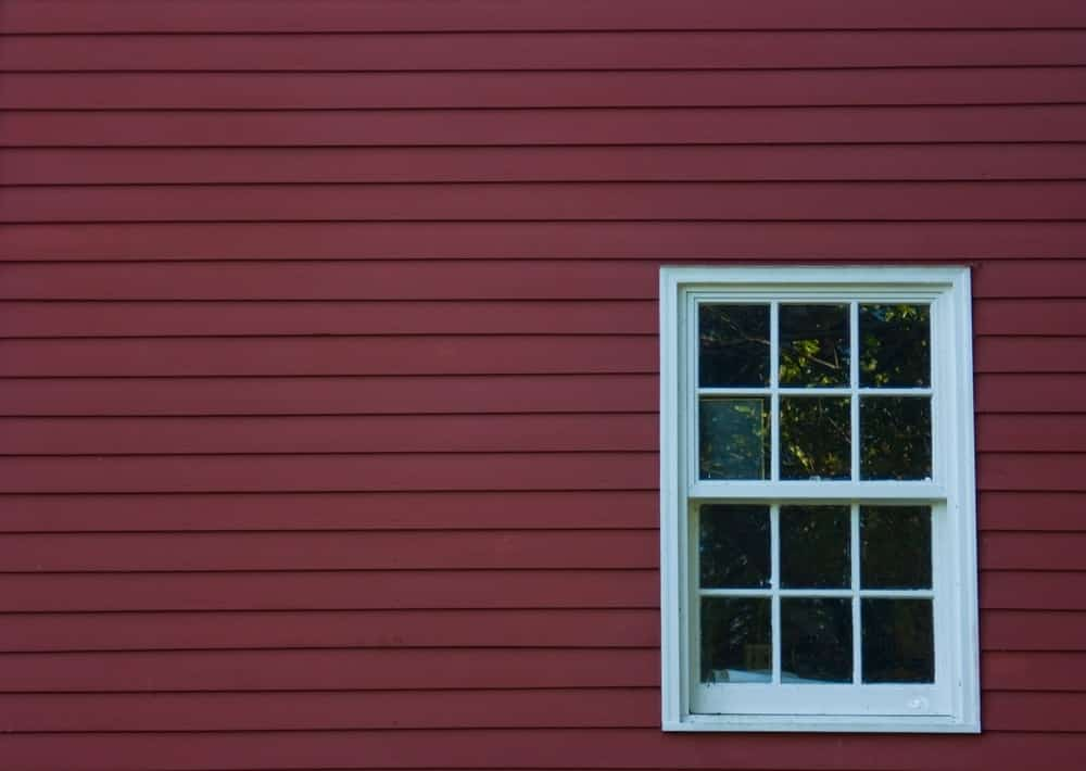 Red mill wall with a hung window.