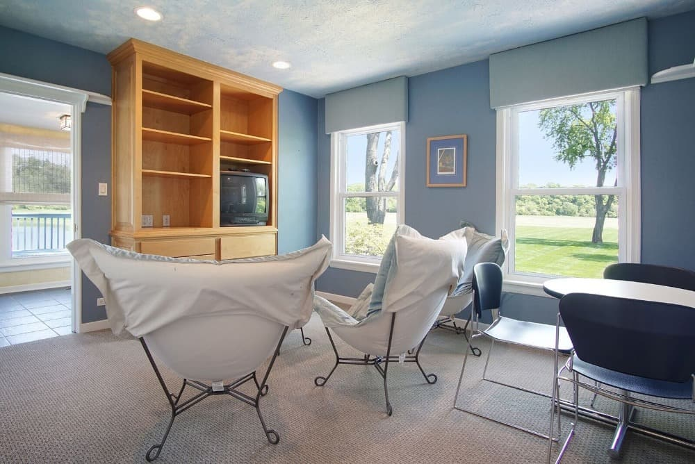 This small living space features carpeted flooring and blueish gray walls. Images courtesy of Toptenrealestatedeals.com.