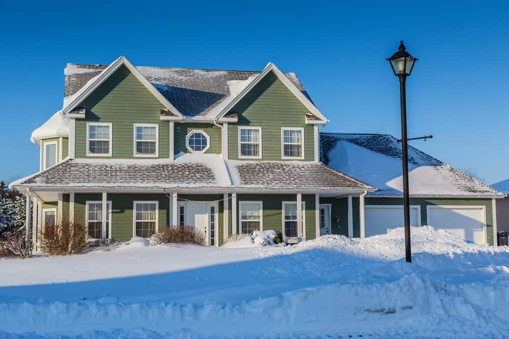 North American family house with green exterior siding after a snowstorm.