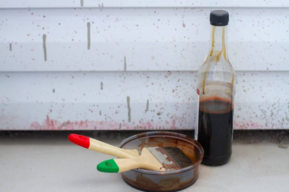 Paint brushes and a bottle beside a concrete and metal siding.