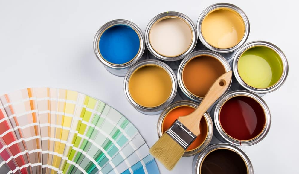 Cans of paint, a paintbrush, and color samples.