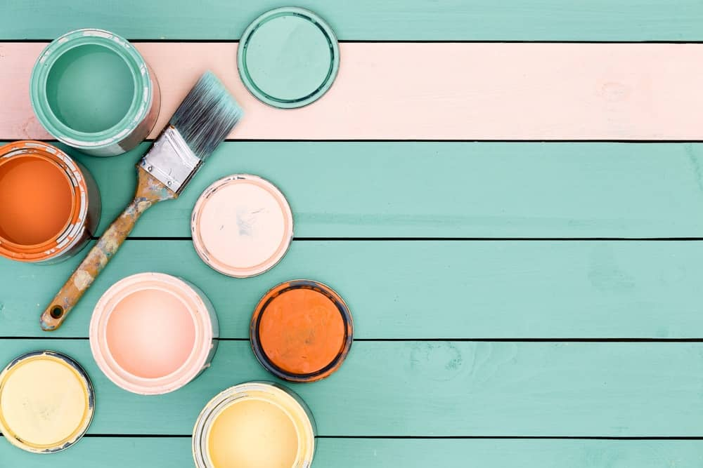 Flat lay of open paint cans and a used paint brush on green floor boards.