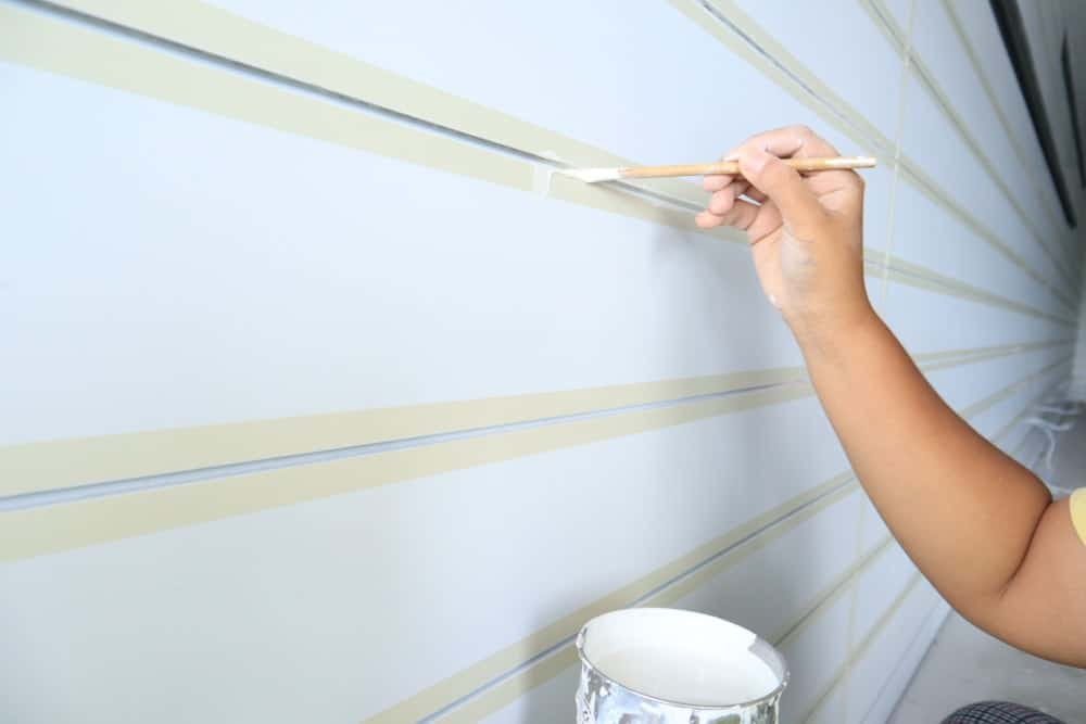 Hand painting the groove on white walls.