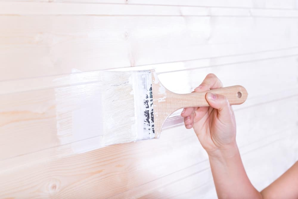 Closeup of the act of painting the wooden slot and key board with white using a brush.