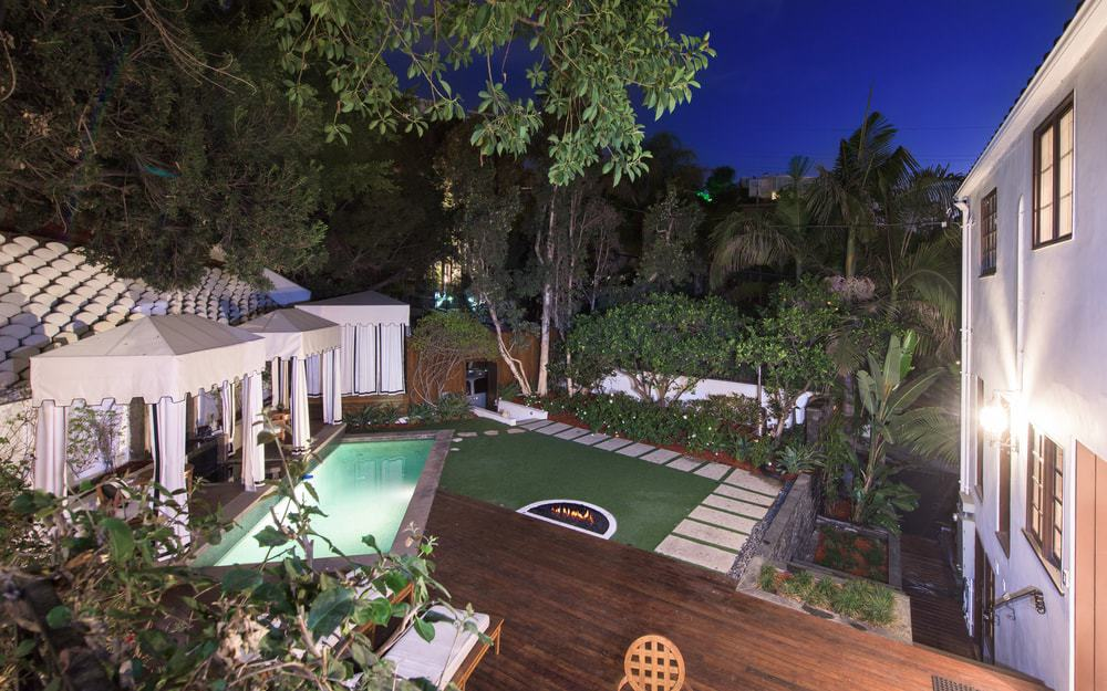 This is the view of the whole backyard from the vantage of the balcony. It has a lawn of grass, a pool and a charming cabana at the far end. Images courtesy of Toptenrealestatedeals.com.