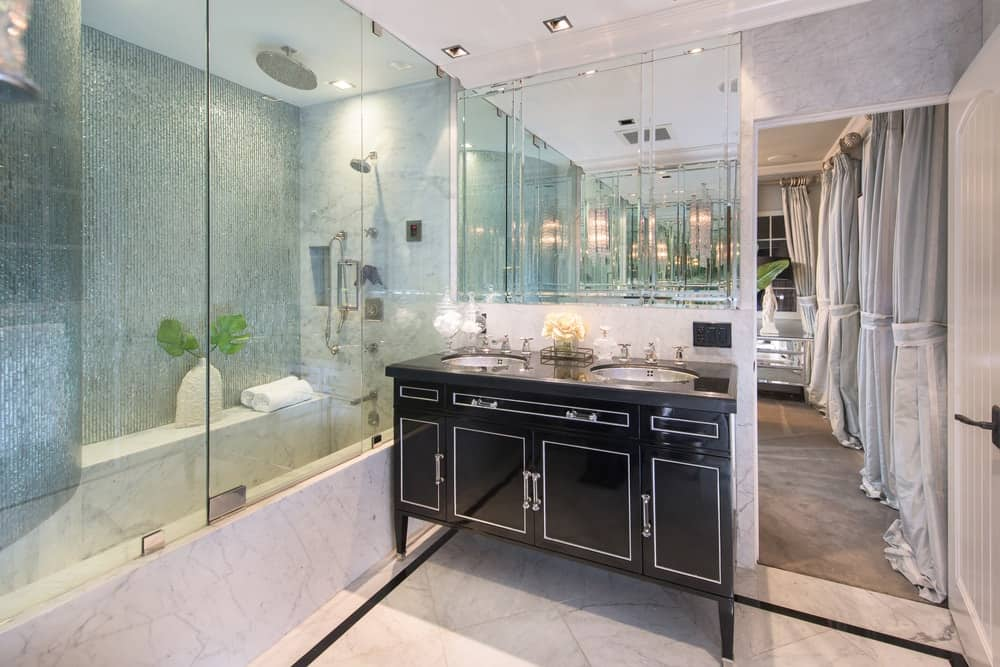 The beautiful bathroom has mirrored walls that augment the brightness of the ceiling and floors contrasted by the dark vanity. Images courtesy of Toptenrealestatedeals.com.