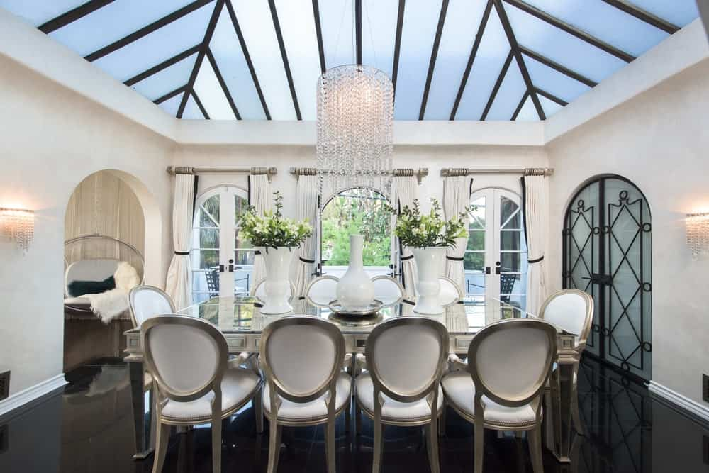 The dining room has an elegant glass-top dining table with a metallic tone to its legs to match the surrounding oval-backed chairs with cushions matching the walls. Images courtesy of Toptenrealestatedeals.com.