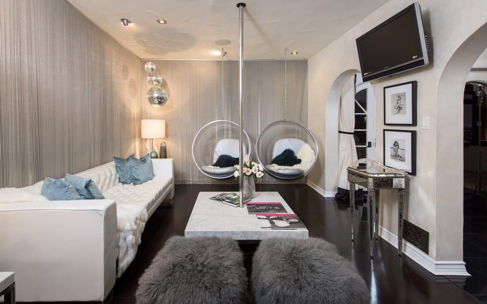 The family room has a long white leather sofa matching with the white marble coffee table fitted with a dancer's pole. These are then contrasted by the dark hardwood flooring. Images courtesy of Toptenrealestatedeals.com.
