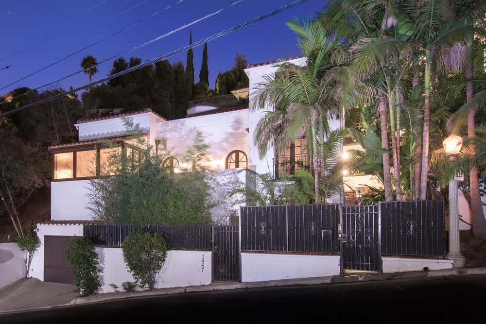 This is front view of this beautiful Spanish-style home with wrought iron fences and gates complemented by the tall trees and shrubs that go well with the white exterior walls of the home. Images courtesy of Toptenrealestatedeals.com.