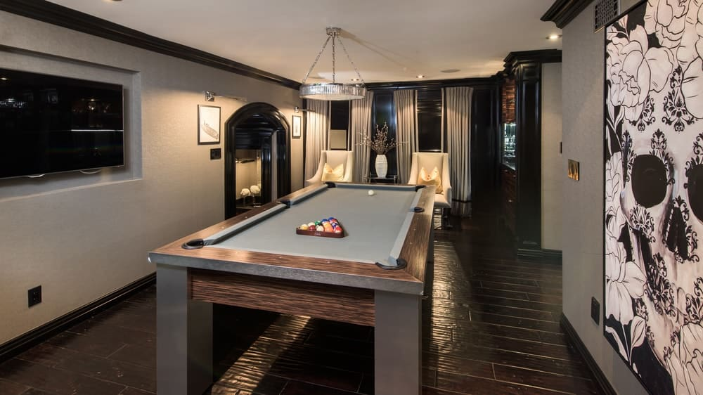 The beautiful game room is dominated by a professional pool table with a dark wooden frame to blend with the dark hardwood flooring complemented by the gray walls. Images courtesy of Toptenrealestatedeals.com.