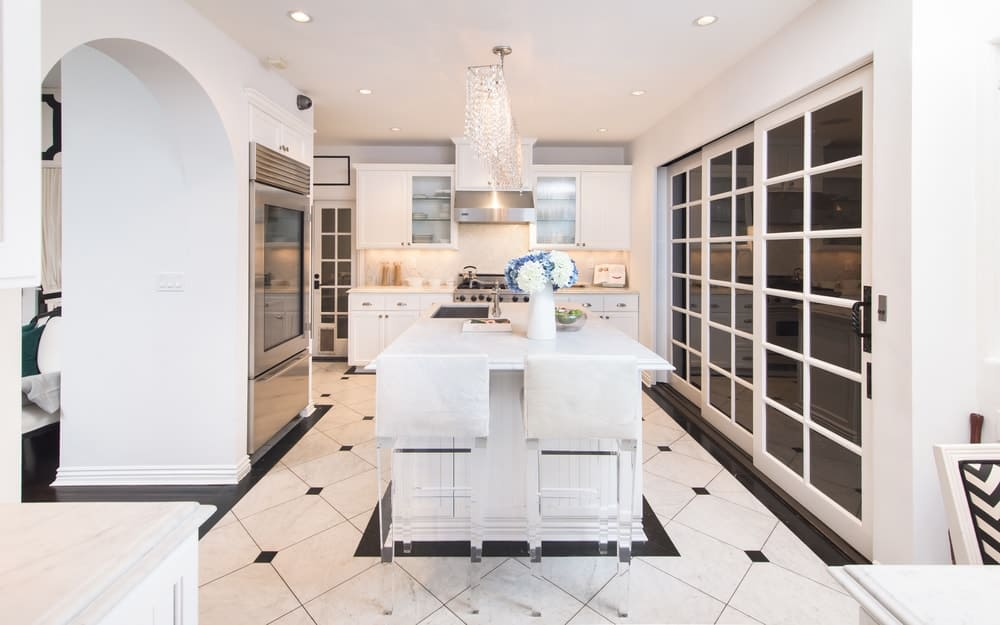 The charming kitchen has a bright ceiling to match the white cabinetry and kitchen island that also serves as the breakfast bar. These bright elements are then complemented by the black details of the floor and silver of the appliances. Images courtesy of Toptenrealestatedeals.com.